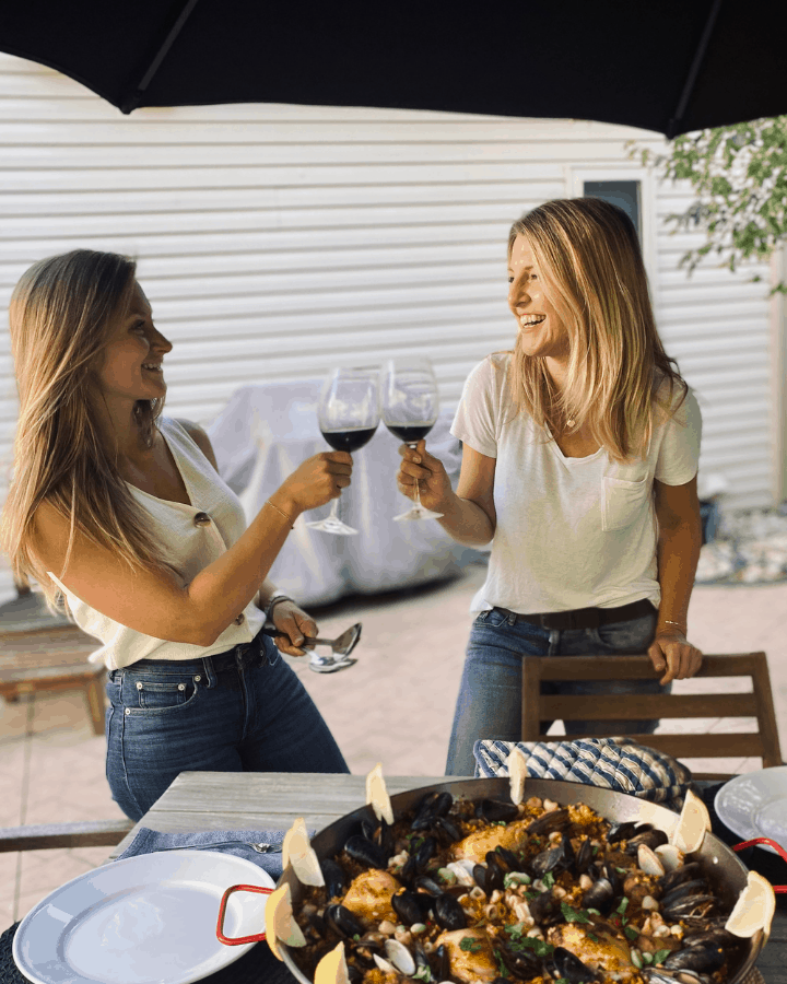 two people toasting with wine glasses in front of large platter of paella
