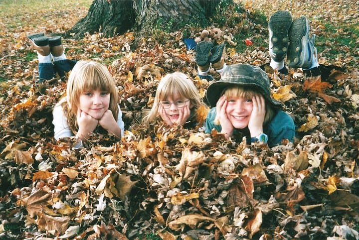three young children in leaves under a tree