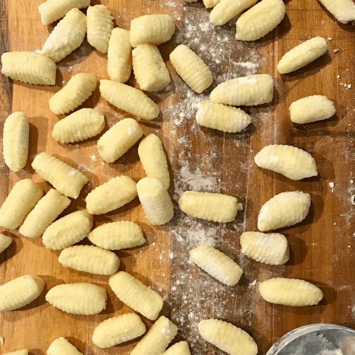Ricotta gnocchi uncooked on wood cutting board