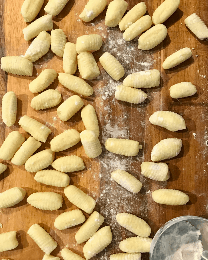 Ricotta gnocchi uncooked on wood cutting board