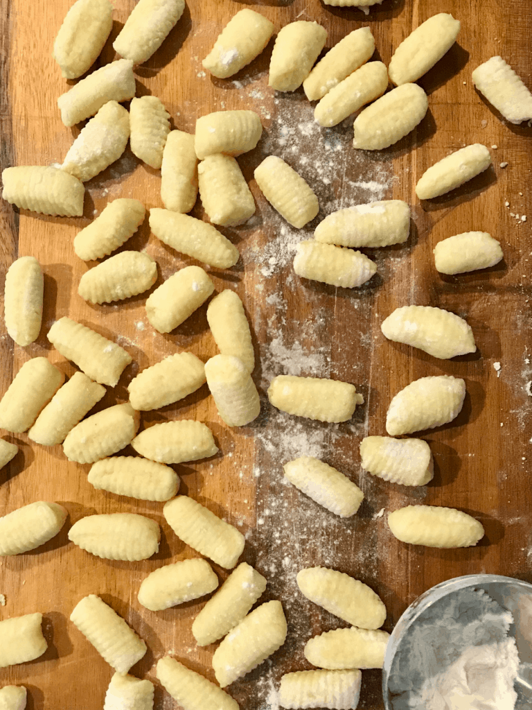 uncooked gnocchi, shaped and on a wooden cutting board