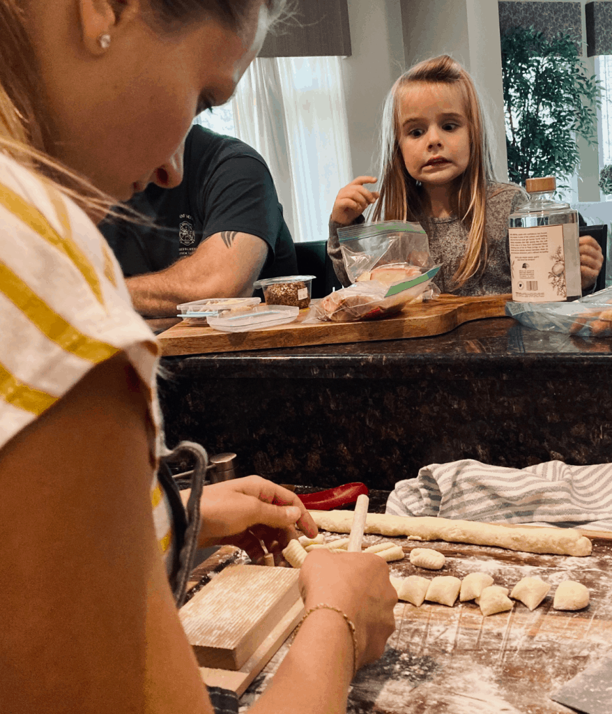 woman shaping gnocchi while little girl watches
