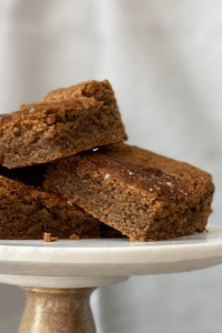 three coffee spice blondies stacked on marble and wood cake stand