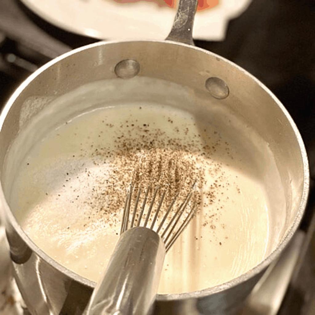 cream sauce and seasonings inside saucepan being whisked