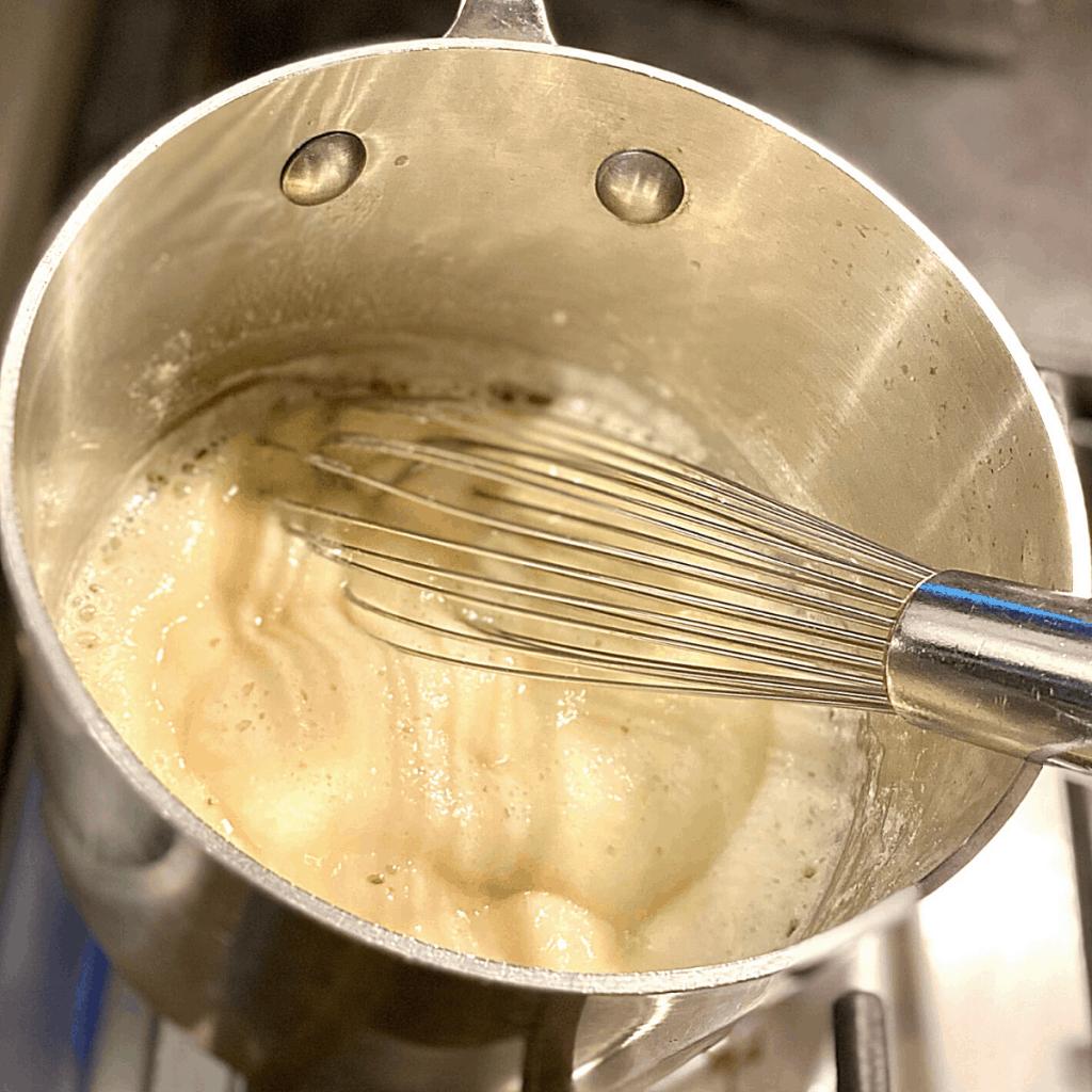 whisking roux in saucepan
