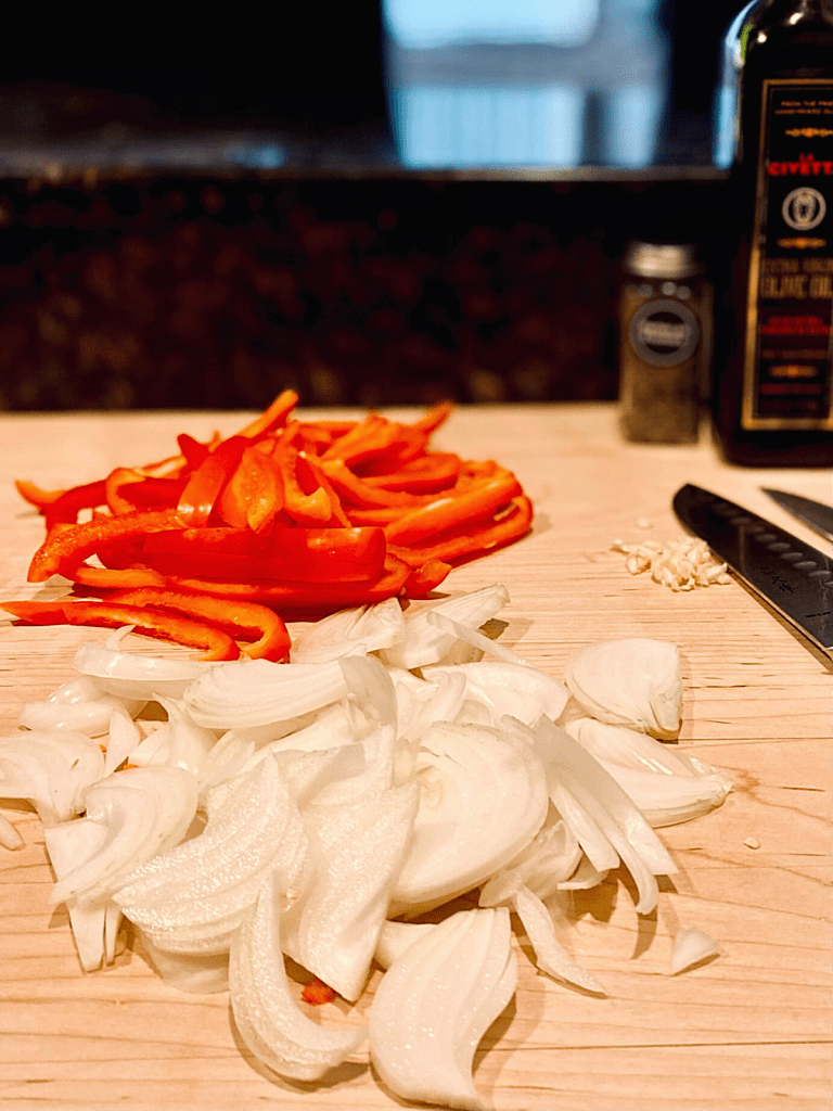 sliced red bell peppers onions and chopped garlic on wood cutting board