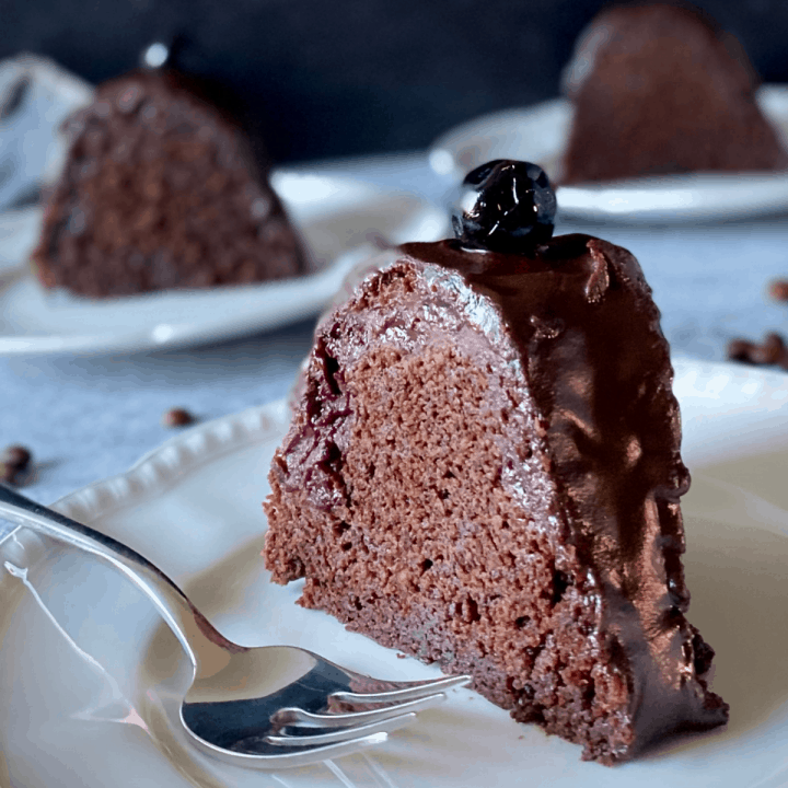 slice of chocolate cake on white plate next to fork with more cake in background