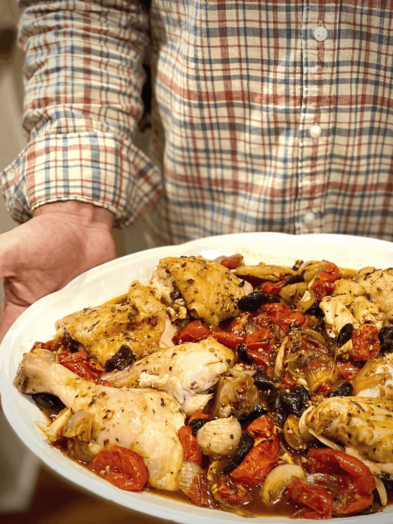 man holding white platter with braised chicken provencal