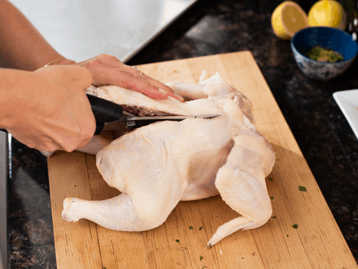 woman's hands using kitchen sheers to cut backbone from raw chicken on wooden cutting board