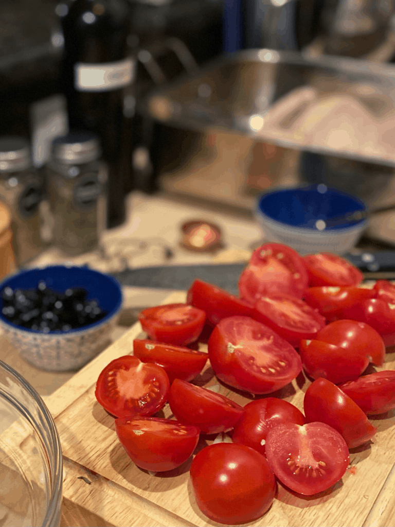 halved tomatoes on cutting board with olives, spices and bowls in background
