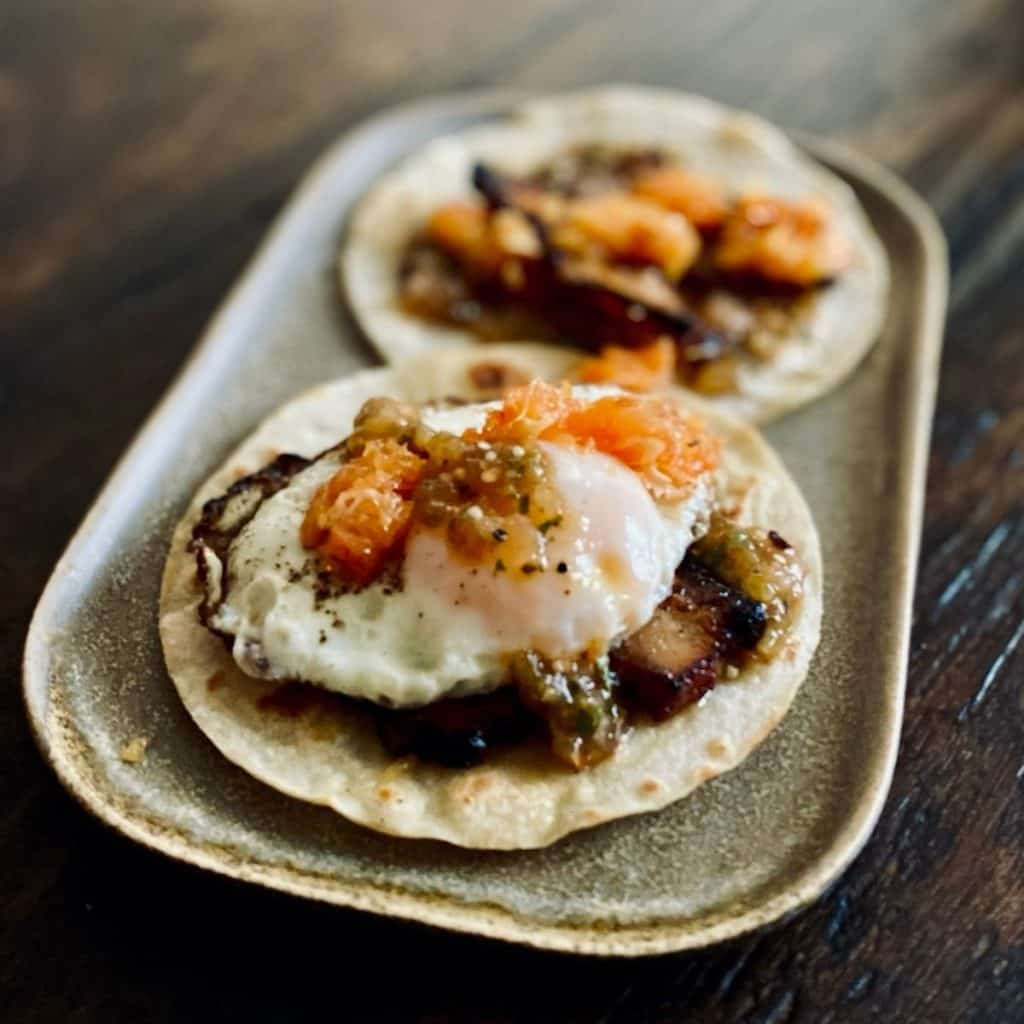 two corn tortillas with pork belly, salsa and fried eggs on square plate