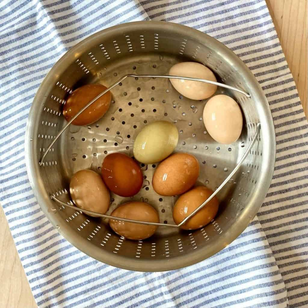 9 eggs in steamer basket on blue and white dish towell