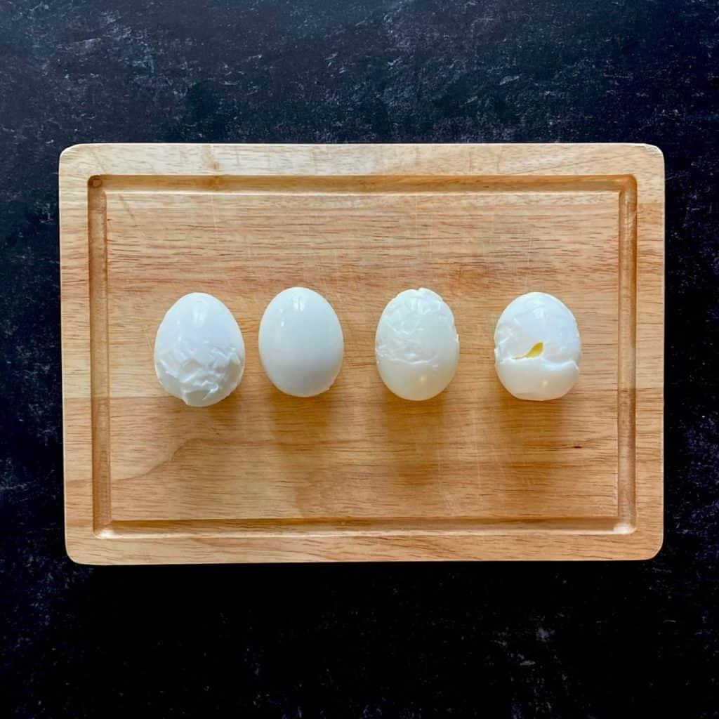 4 hardboiled peeled eggs on wood board