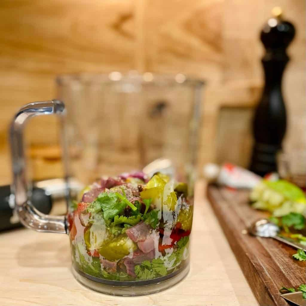 clear pitcher filled with salsa ingredients