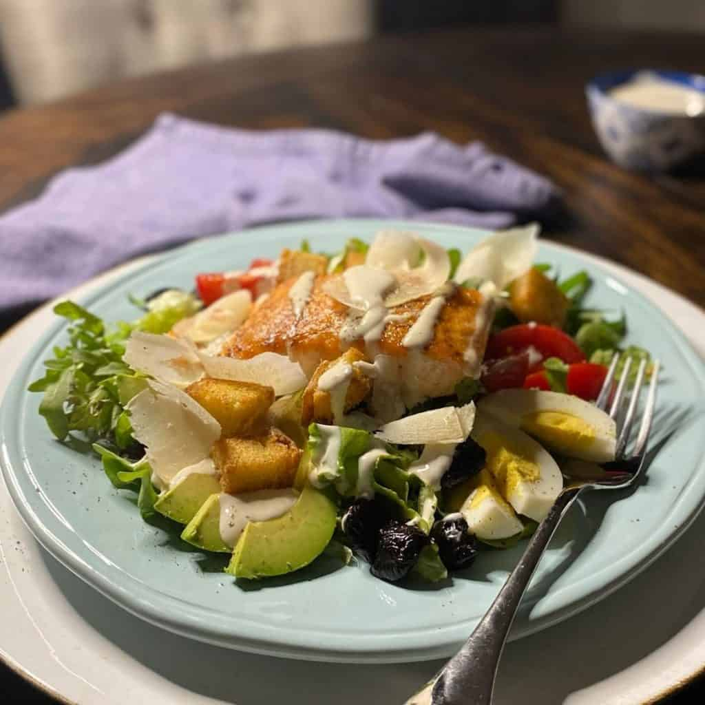 salad of salmon, olives, avocado and eggs on blue plate