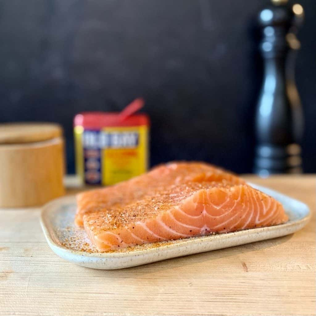 two raw pieces salmon on plate with seasoning