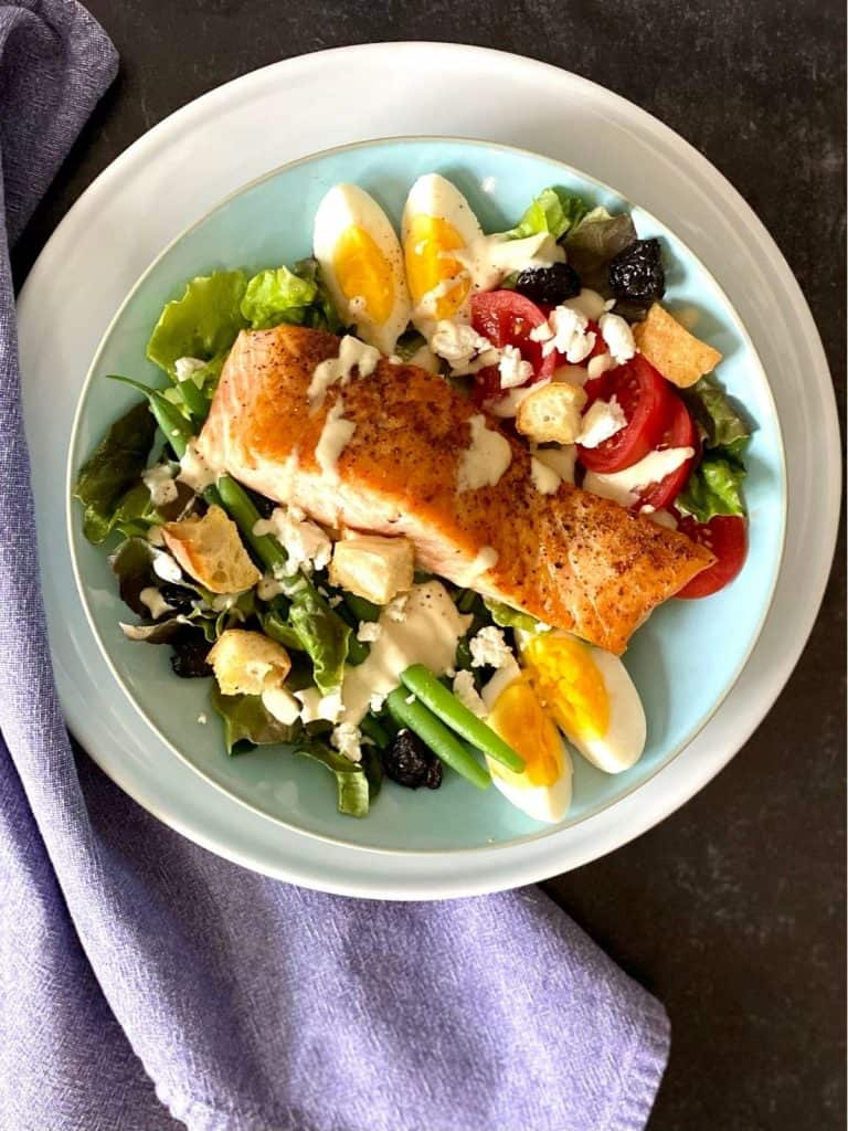 salmon salad on blue and white plate with napkin