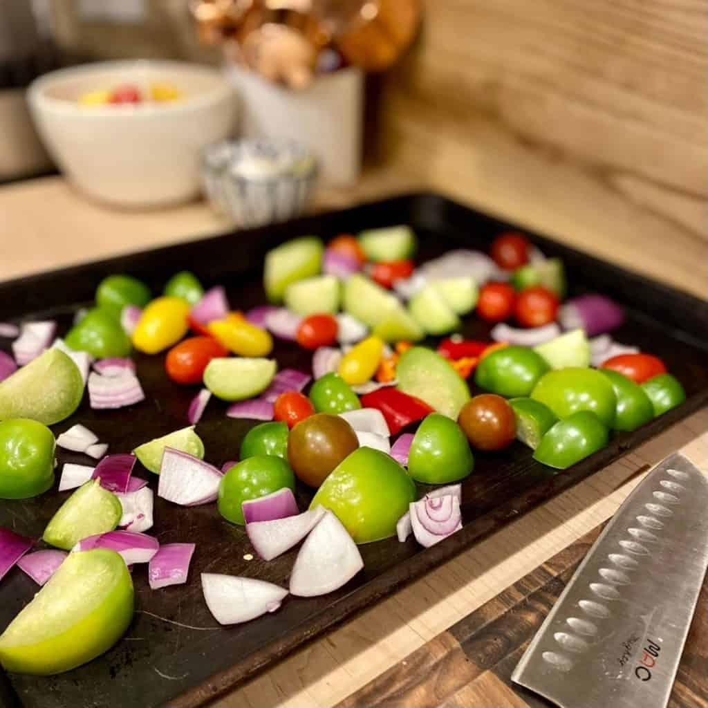 raw salsa ingredients on baking sheet next to knife