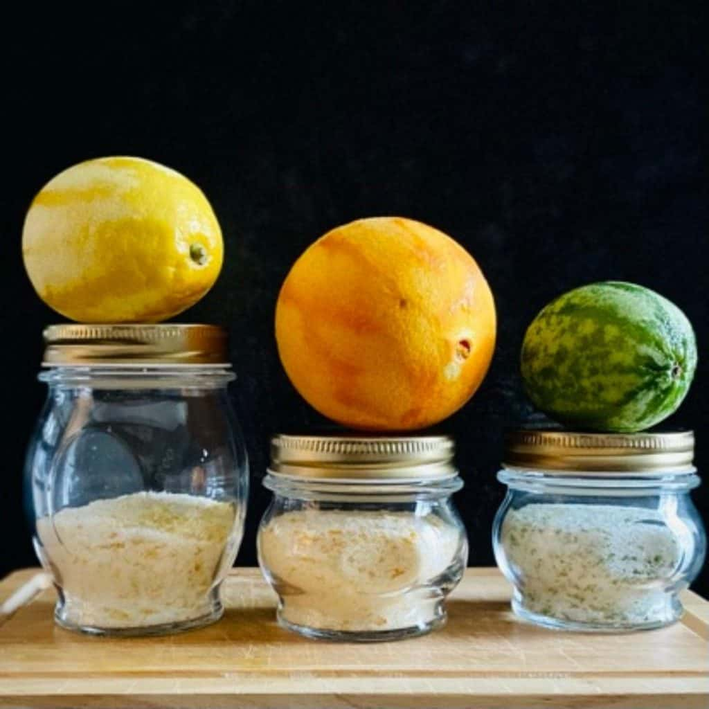 3 jars of citrus salt with zested piece of fruit on top of each