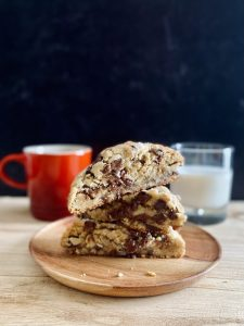 3 chocolate chip cookie halves stacked on wood plate in front of glass of milk and coffee mug