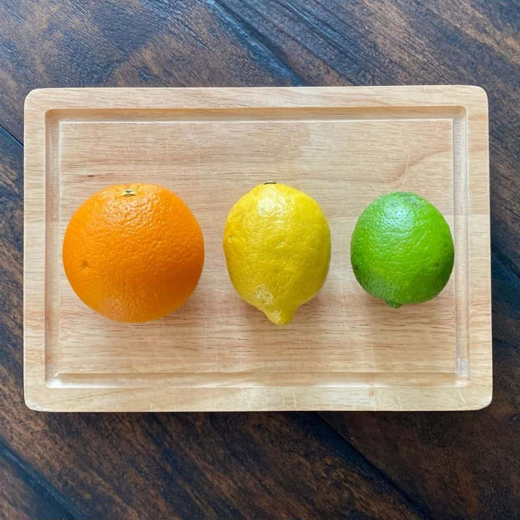 orange, lemon and lime on wood cutting board