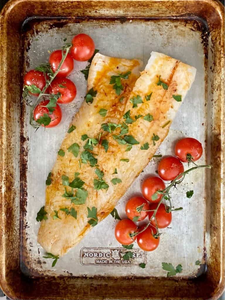 baking sheet with stem tomatoes and seasoned cod uncooked