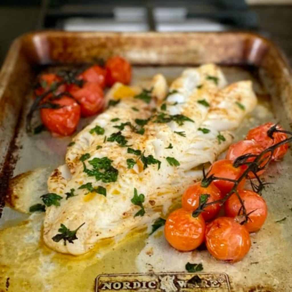 Cooked stem tomatoes and cod on baking sheet
