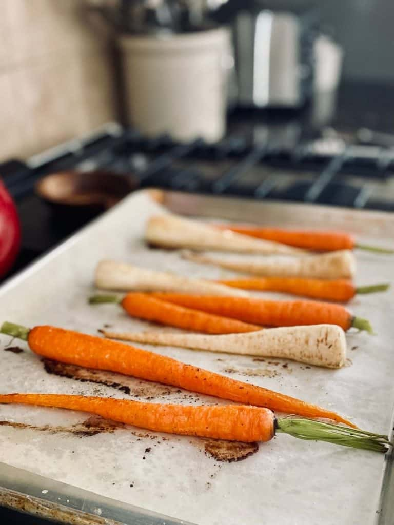 parchment lined baking sheet with roasted root vegetables on top of stove