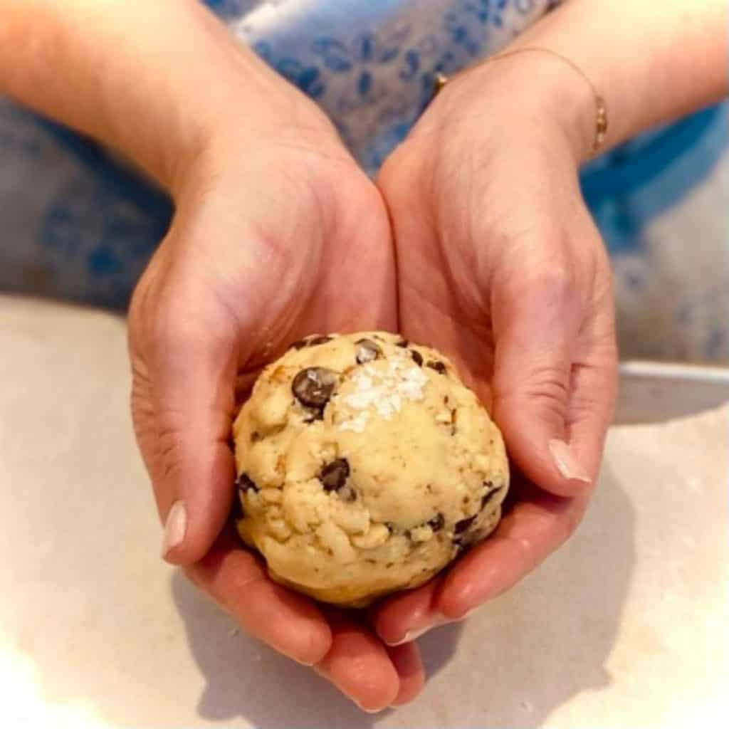 two hands holding large cookie dough ball