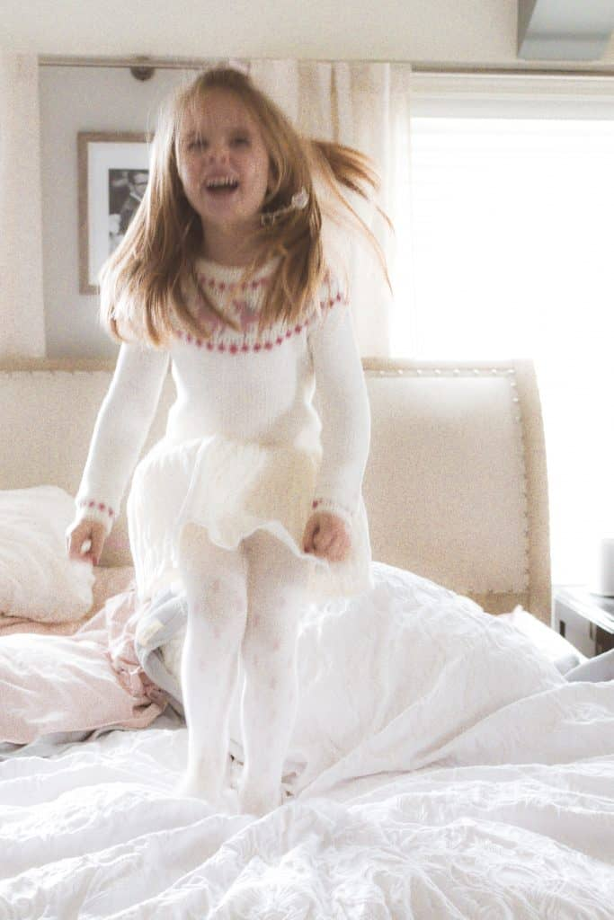 happy little girl jumping on a bed