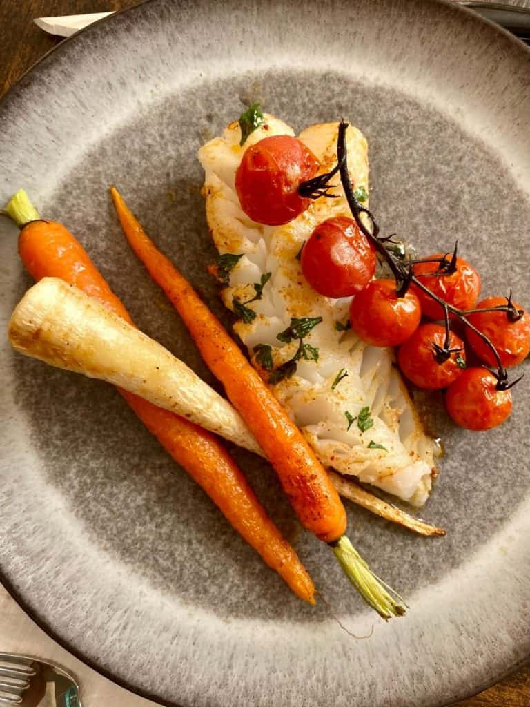 broiled cod and stem tomatoes with roasted root vegetables on grey plate