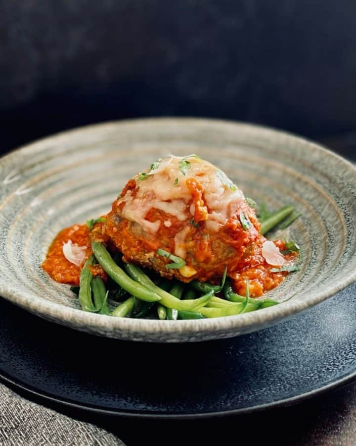 side view of meatball, green beans and sauce in bowl