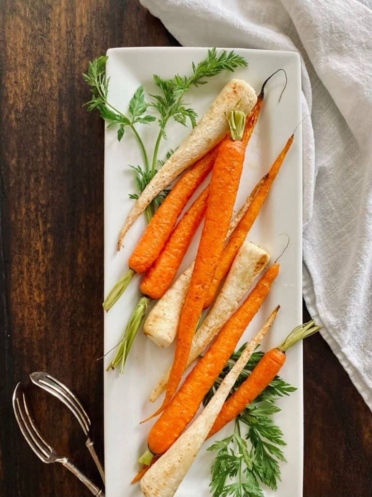 long, white platter with roasted carrots & parsley root garnished with carrot top fronds