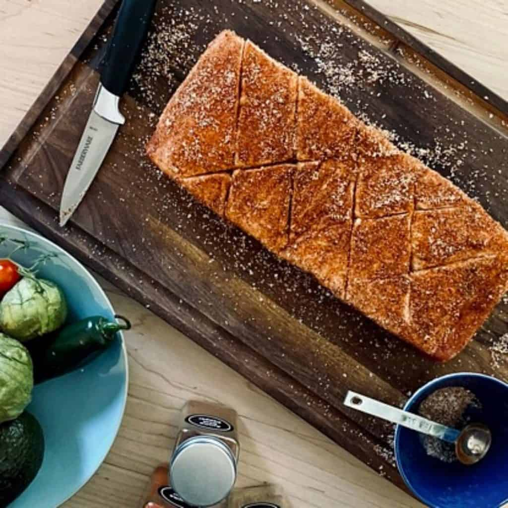 raw pork belly rubbed with spices on wood board with paring knife surrounded by spices and bowl of avocado, jalapeno and tomatillos