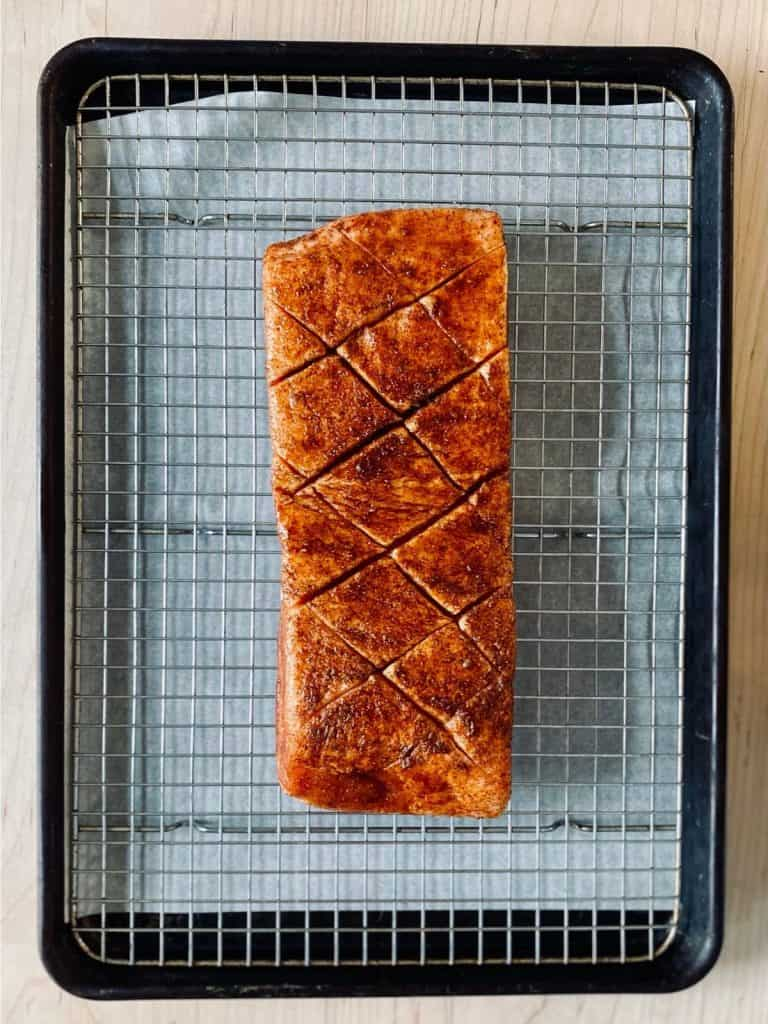 scored, seasoned pork belly from top on rack over jelly roll pan