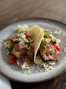 pork belly tacos on grey plate