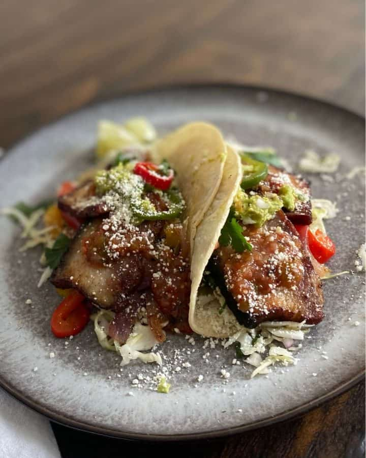 pork belly tacos on grey plate
