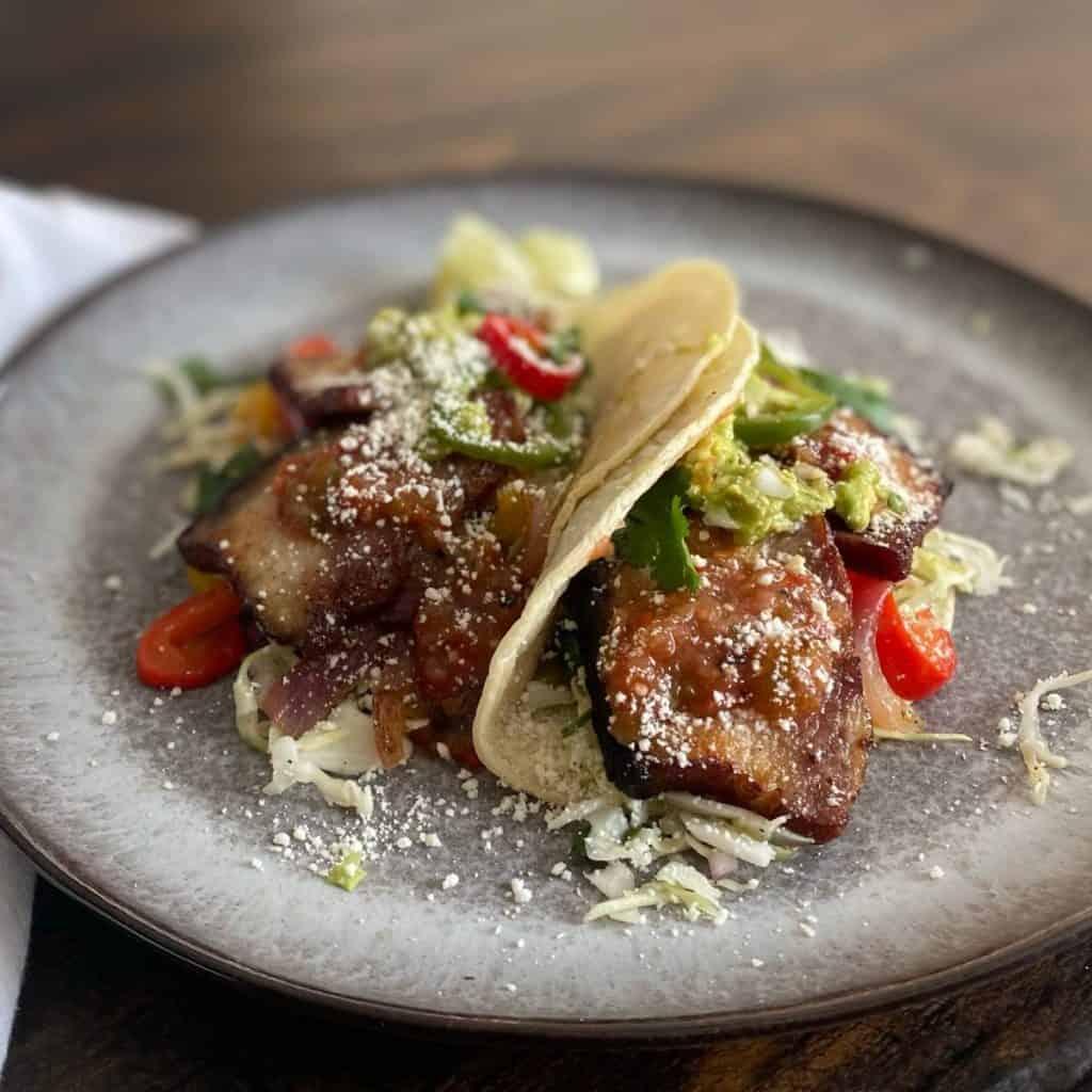 2 pork belly tacos on grey plate