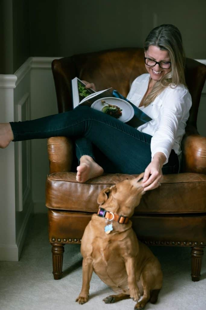 woman sitting in leather chair with book petting dog on the floor