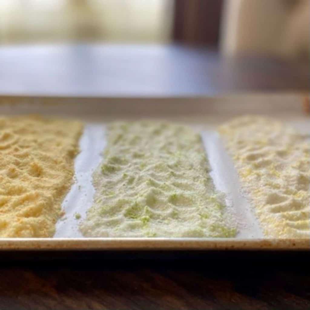 rimmed baking sheet with orange salt, lemon salt and lime salt in strips