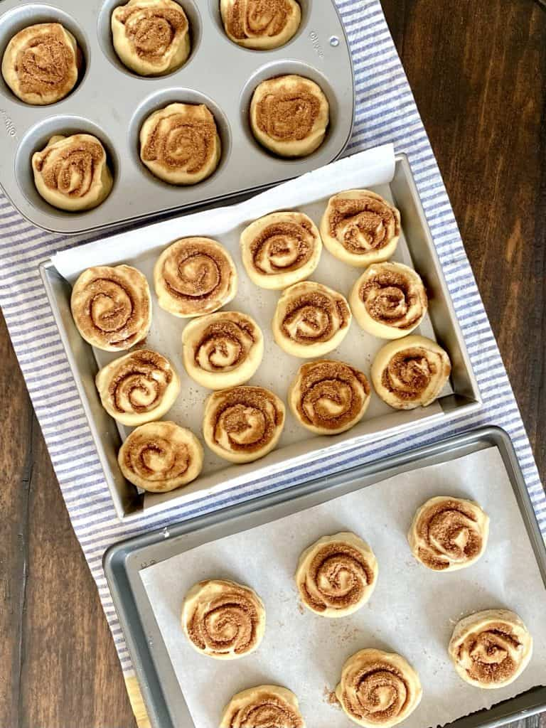 three pans of unbaked cinnamon rolls on top of blue and white striped towell