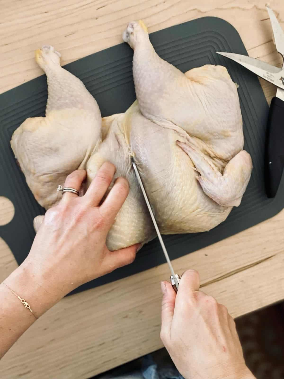 flattened chicken on cutting board with hands using cleaver to cut in half