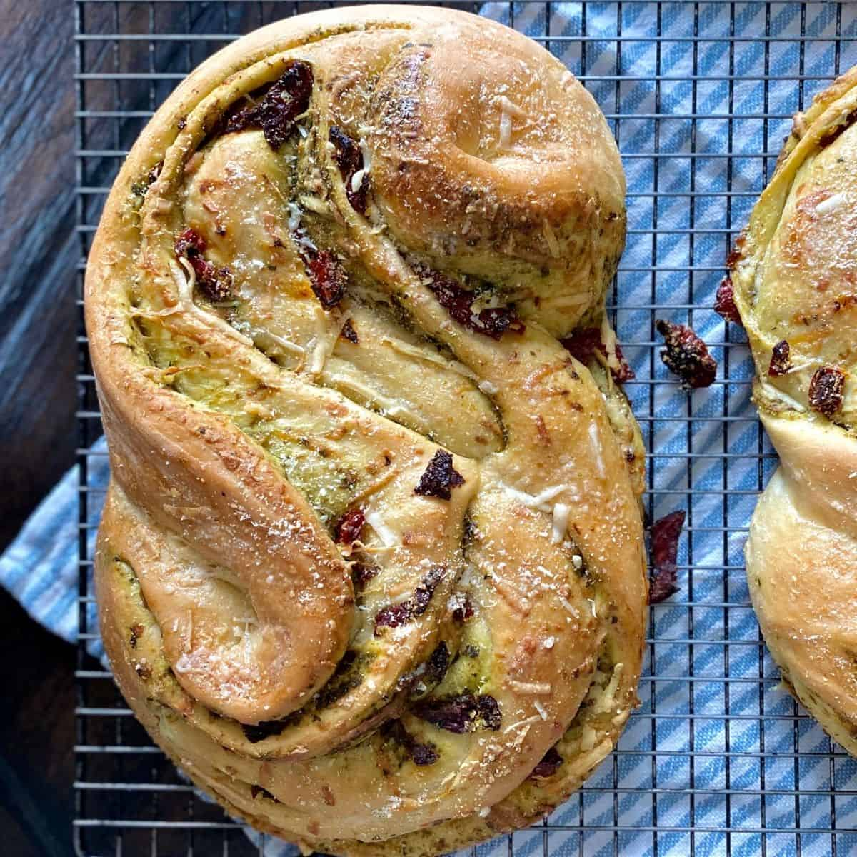 baked bread stuffed with pesto and sindried tomatoes on cooling rack