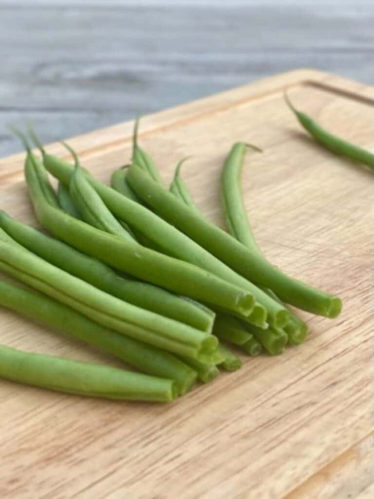 bunch of trimmed green beans on cutting board