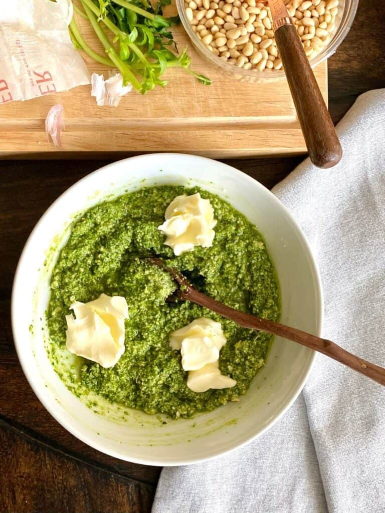 white bowl of pesto with dabs of butter on top and wooden spoon