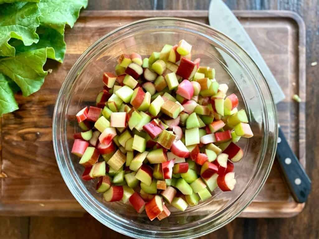 bowl of diced rhubarb next to knife on wood board