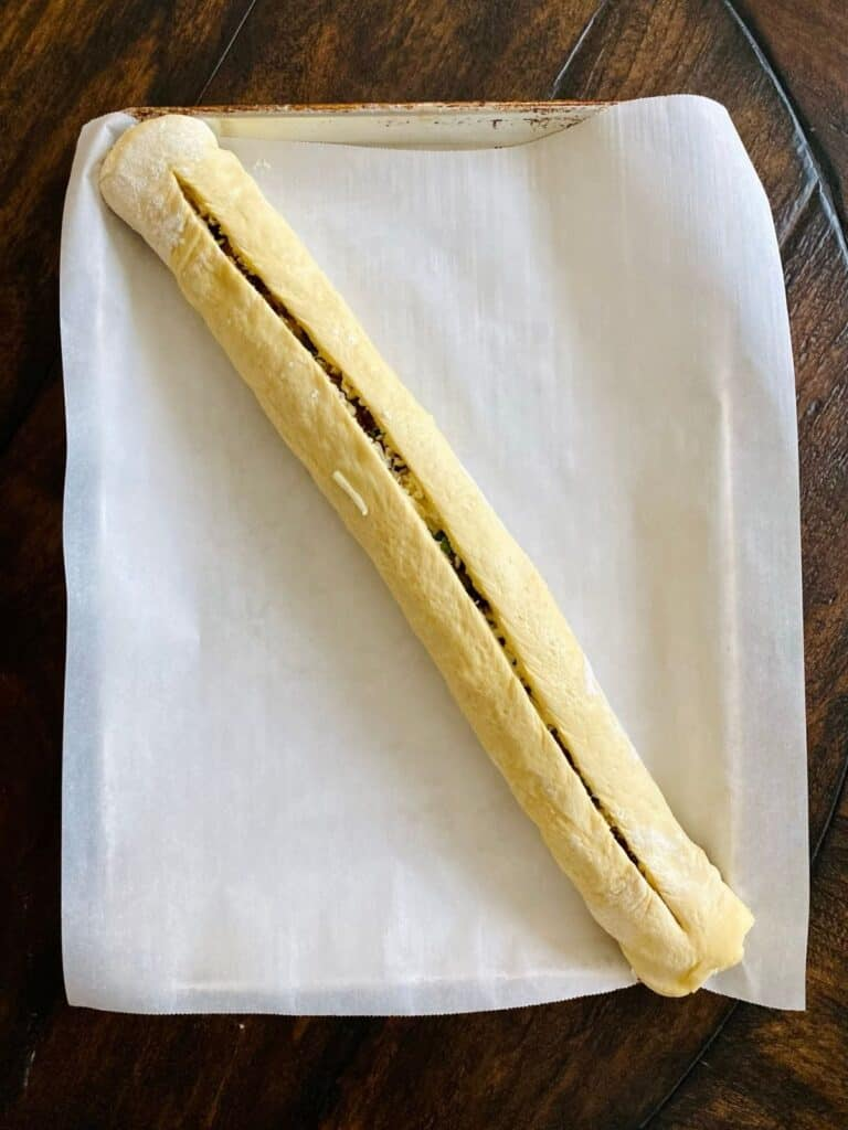filled bread dough shaped into a log on parchment