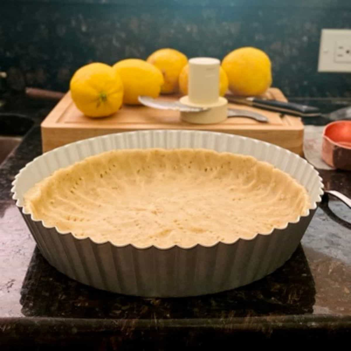 tart pan with unbaked tart dough on counter in front of lemons