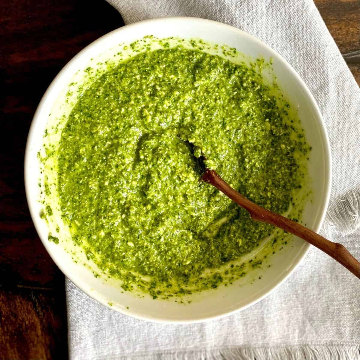 white bowl of pesto on grey towel with wooden spoon