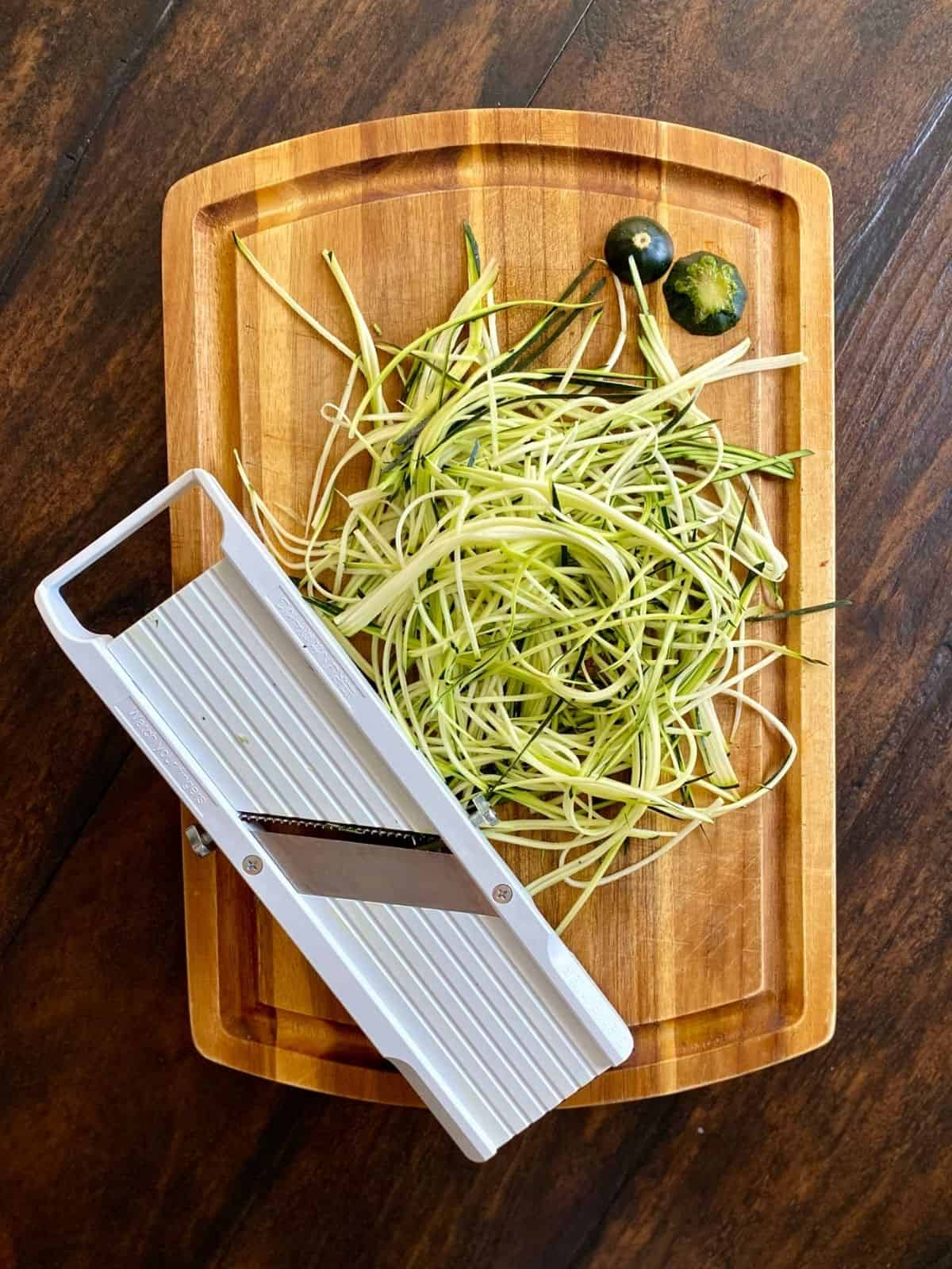 wood cutting board topped with julienned zucchini next to mandoline